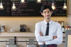 Jeune homme se tenant au compteur de café Mâle au travail en café SH photo libre de droits