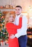 Jeune homme se tenant avec la femme portant la robe rouge près de l'arbre de Cristmas Photographie stock