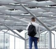 Jeune homme se tenant dans l'aéroport vide Photographie stock libre de droits