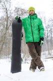 Jeune homme se tenant dans la neige d'un surf des neiges Images libres de droits