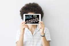 Jeune homme se tenant de nouveau au comprimé numérique écrit par école Images stock