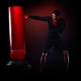 Jeune homme se tenant s'exerçant avec le sac de boxe Image libre de droits