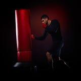 Jeune homme se tenant s'exerçant avec le sac de boxe Images libres de droits