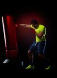 Jeune homme se tenant s'exerçant avec le sac de boxe Images stock