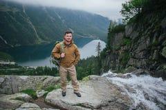Jeune homme se tenant sur la falaise en montagnes d'été au coucher du soleil image stock