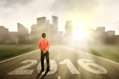Jeune homme se tenant sur la route avec les numéros 2016 Photo stock