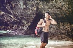 Jeune homme se tenant sur le bord de l'océan Image stock