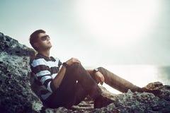 Jeune homme se tenant sur une falaise au coucher du soleil Photos libres de droits