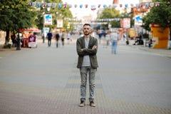 Jeune homme se tenant tranquille au trottoir avec des personnes se déplaçant autour Photographie stock libre de droits