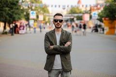 Jeune homme se tenant tranquille au trottoir avec des personnes se déplaçant autour Image libre de droits