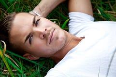 Jeune homme se trouvant sur des gras verts photographie stock libre de droits