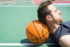 Jeune homme se trouvant sur un basket-ball images stock
