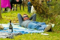 Jeune homme se trouvant sur une couverture de pique-nique à l'événement de vin Photos stock