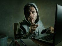 Jeune homme semblant dangereux de pirate informatique dans le hoodie dactylographiant sur l'ordinateur portable entaillant et don photos libres de droits
