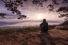 Jeune homme seul reposant extérieur sur la falaise Photographie stock
