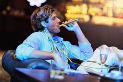 Jeune homme seul s'asseyant dans la barre avec un verre de whiskey photos libres de droits