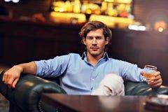 Jeune homme seul s'asseyant dans la barre avec un verre de whiskey photographie stock