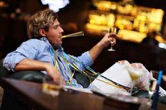 Jeune homme seul s'asseyant dans la barre avec un verre de whiskey images stock