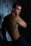 Jeune homme sexy avec un torse nu sur un fond foncé photo libre de droits