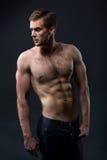 Jeune homme sexy avec un torse nu sur un fond foncé images stock