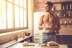 Jeune homme sexy dans la cuisine image stock