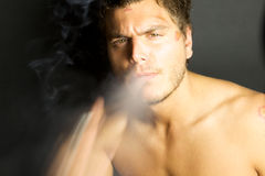 Jeune homme sexy fumant une cigarette image stock