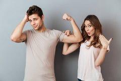 Jeune homme sexy montrant le biceps à son amie stupéfaite Image stock