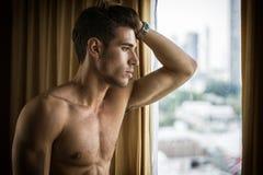 Jeune homme sexy se tenant sans chemise par des rideaux image libre de droits