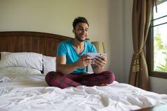 Jeune homme Sit On Bed, téléphone heureux de Guy Bedroom Using Cell Smart d'hispanique de sourire photographie stock