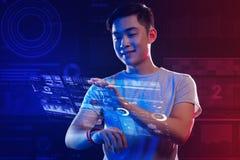 Jeune homme soigneux faisant une projection avec une aide de sa montre intelligente photographie stock