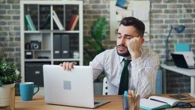 Jeune homme somnolent travaillant avec l'ordinateur portable dans le bureau faisant une sieste alors sur le bureau clips vidéos