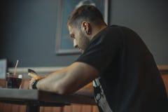 Jeune homme songeur attirant regardant l'écran de téléphone portable et buvant la soude image libre de droits