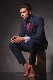 Jeune homme songeur d'affaires s'asseyant avec ses mains ensemble images libres de droits