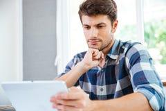 Jeune homme songeur pensant et à l'aide du comprimé à la maison Photo libre de droits