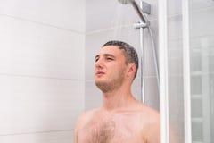 Jeune homme songeur prenant une douche dans la salle de bains Photos libres de droits