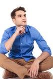 Jeune homme songeur s'asseyant avec ses jambes croisées Photos stock