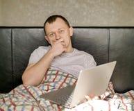 Jeune homme songeur s'asseyant dans le lit avec un ordinateur portable, regardant directement la caméra images stock
