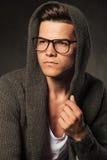 Jeune homme songeur utilisant un hoodie gris Image stock