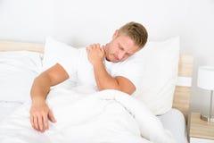 Jeune homme souffrant de la douleur d'épaule Photographie stock