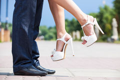 Jeune homme soulevant sa mariée vers le haut à l'extérieur Image stock