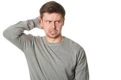 Jeune homme soumis à une contrainte avec l'expression perplexe incertaine, sur le fond blanc Photographie stock libre de droits