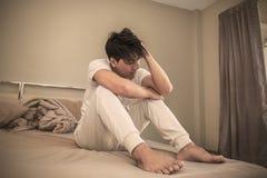 Jeune homme soumis à une contrainte sur son lit image stock
