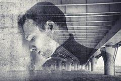 Jeune homme soumis à une contrainte triste avec le fond de mur en béton Image stock