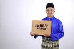 Jeune homme souriant avec le tableau pour la célébrité d'Eid Fitr ou d'Eid Adha Images stock