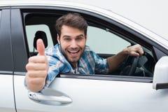 Jeune homme souriant et montrant des pouces  Image libre de droits