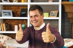 Jeune homme souriant et montrant deux pouces  Photos libres de droits