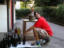 Jeune homme souriant tout en mettant le vin en bouteille à la maison image stock