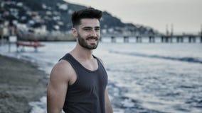 Jeune homme sportif attirant marchant sur la plage images libres de droits