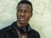 Jeune homme sportif beau et attirant d'Afro-am?ricain dans la veste noire ouverte de denim posant dans l'attitude fra?che dans la photo libre de droits