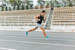 Jeune homme sportif courant sur le stade pendant le matin Photos stock